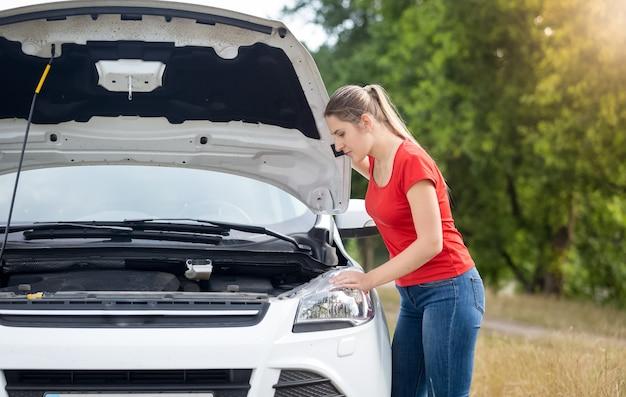 Jovem chateada olhando sob o capô de um carro superaquecido no campo