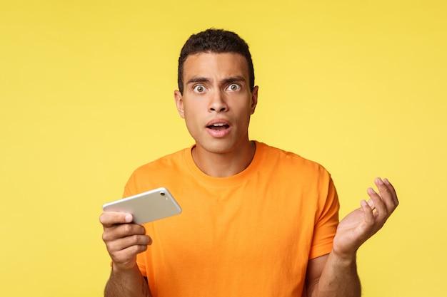 Jovem chateado e questionado não consegue entender como ele perdeu no jogo, olha a câmera perplexo, segurando o smartphone horizontalmente, levanta o braço em desânimo e tristeza, em pé em fundo amarelo