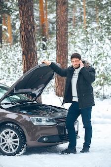 Jovem chateado, ligando para o serviço de carro em pé sobre o carro quebrado no inverno na floresta. carro de assistência rodoviária