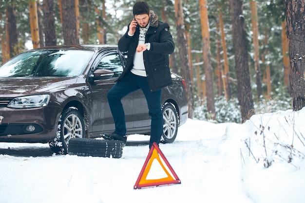 Jovem chateado, ligando para o serviço de carro em pé sobre o carro quebrado no inverno na floresta.