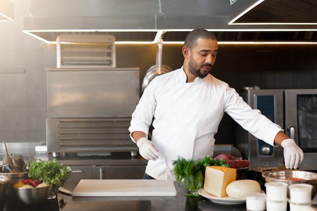 Jovem chef africano bonito cozinhando