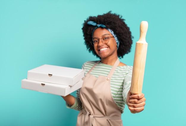 Jovem chef afro com um rolo de massa e pizzas