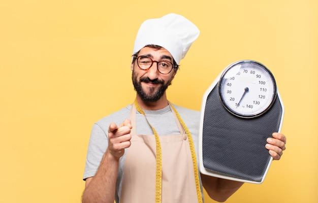 Jovem chef barbudo apontando ou mostrando e segurando uma balança