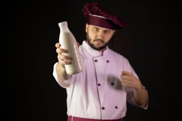 Jovem chef barbudo confiante de uniforme apontando o dedo indicador para uma garrafa de plástico de leite