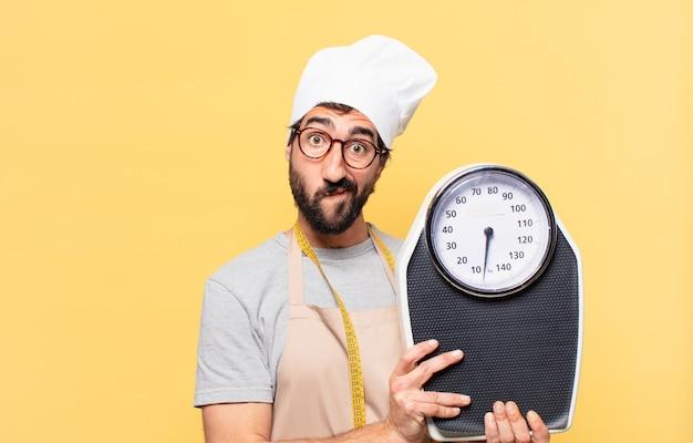 Jovem chef barbudo duvidando ou com uma expressão incerta e segurando uma balança