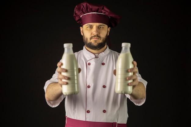 Jovem chef barbudo sério de uniforme segurando duas garrafas plásticas de leite