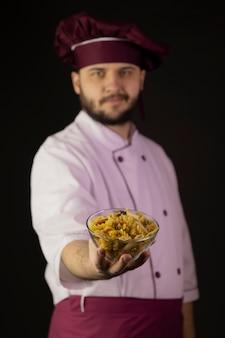 Jovem chef barbudo sorridente de uniforme guarda uma tigela de macarrão