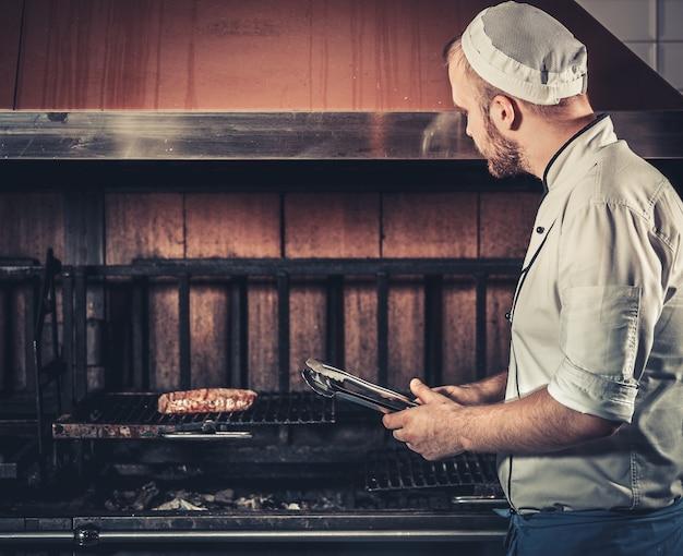 Jovem chef branco com avental azul e chapéu em pé perto do braseiro com brasas. homem cozinhando bife no interior de uma moderna cozinha profissional