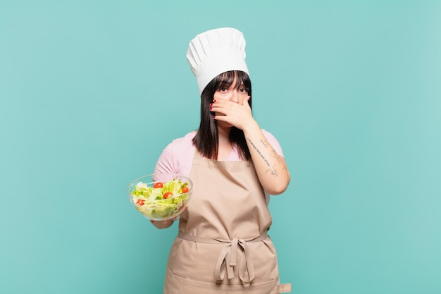 Jovem chef cobrindo a boca com as mãos com uma expressão chocada e surpresa, mantendo um segredo ou dizendo oops
