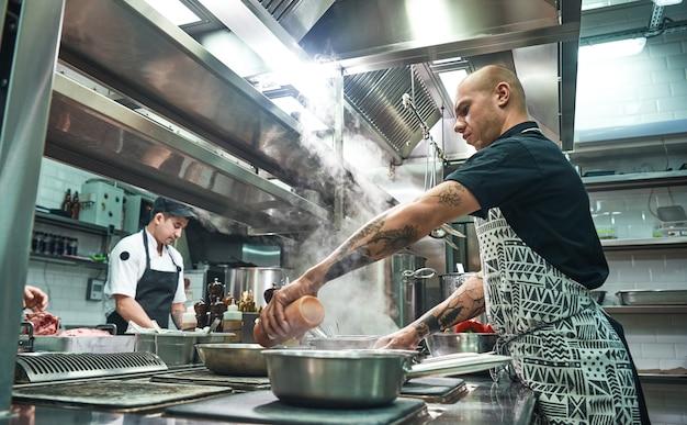 Jovem chef concentrado de avental e cozinheiros preparando comida juntos na cozinha de um restaurante