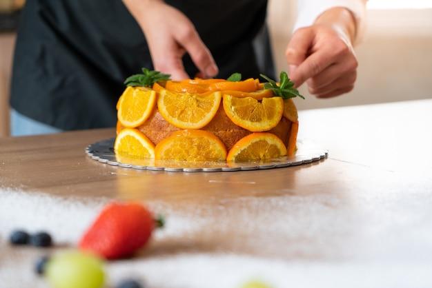 Jovem chef confeiteiro cozinhando um bolo de laranja com laranjas fatiadas