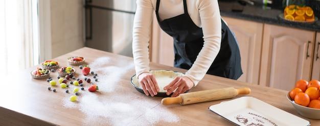 Jovem chef confeiteiro cozinhando um bolo doce na cozinha