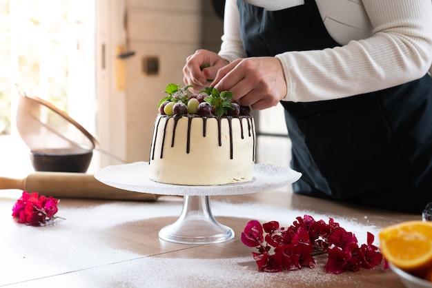Jovem chef confeiteiro cozinhando um delicioso bolo caseiro de chocolate com frutas na cozinha