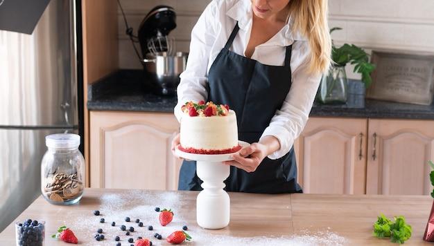 Jovem chef confeiteiro cozinhando um tradicional bolo de veludo vermelho na cozinha