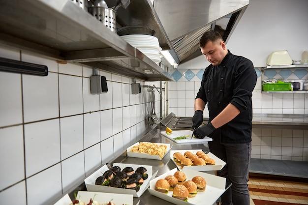 Jovem chef de cozinha em túnica preta prepara lanches de catering