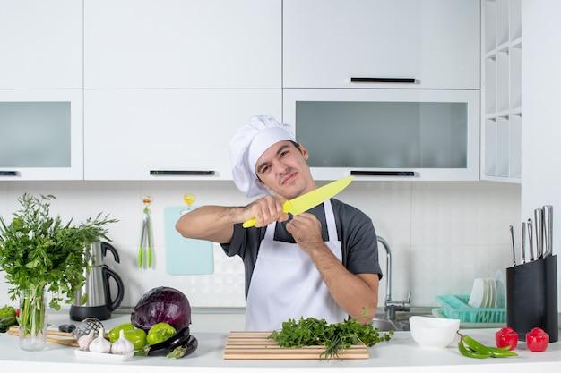 Jovem chef de uniforme na cozinha, vista frontal, vegetais diferentes na mesa