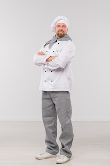 Jovem chef do sexo masculino de sucesso com os braços cruzados no peito, olhando para você enquanto está isolado