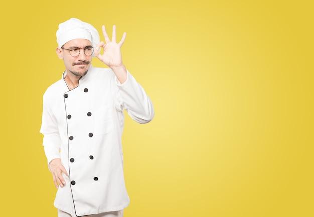 Jovem chef espantado, usando as mãos como um binóculo