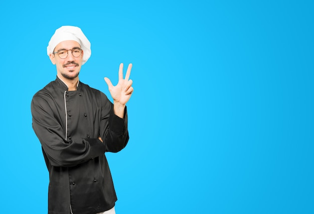 Jovem chef fazendo um gesto de número três