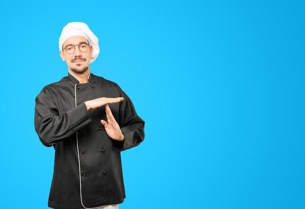 Jovem chef fazendo um gesto de tempo limite com as mãos