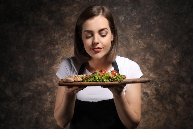 Jovem chef feminina com saboroso prato escuro