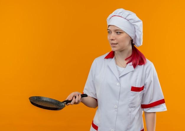 Jovem chef feminina loira satisfeita com uniforme de chef segura a frigideira e olha para o lado isolado na parede laranja
