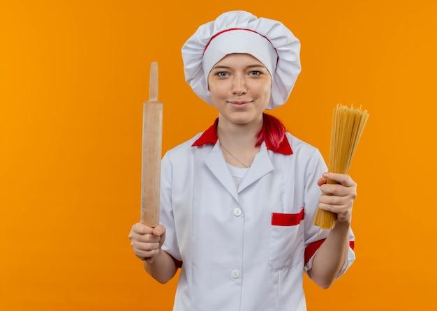 Jovem chef feminina loira satisfeita com uniforme de chef segurando molho de espaguete e rolo de massa isolado na parede laranja