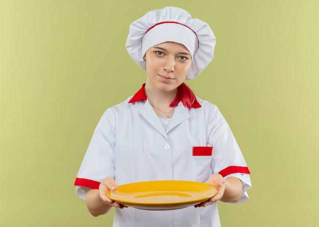 Jovem chef feminina loira satisfeita com uniforme de chef segurando o prato isolado na parede verde