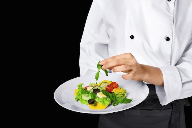 Jovem chef feminina segurando o prato com salada em uma superfície escura.