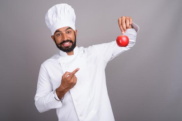 Jovem chef indiano segurando uma maçã