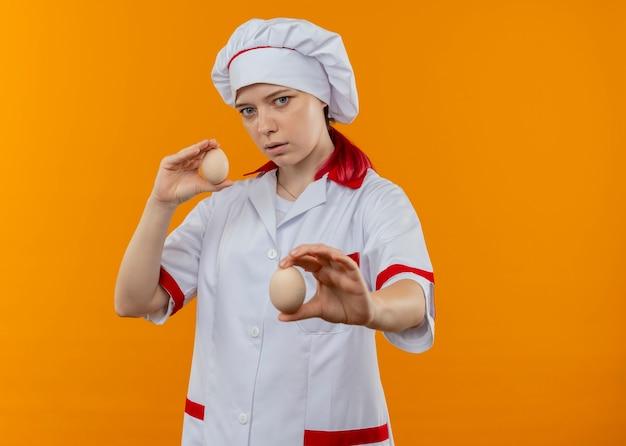 Jovem chef loira confiante com uniforme de chef segurando ovos isolados na parede laranja