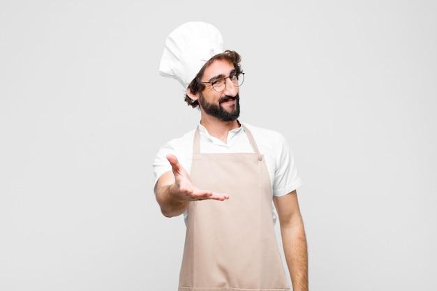 Jovem chef louco sorrindo, olhando feliz, confiante e amigável, oferecendo um aperto de mão para fechar um acordo, cooperando sobre parede branca