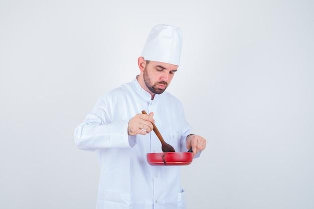 Jovem chef masculino em uniforme branco, mistura de refeição com colher de pau e olhando curioso, vista frontal.