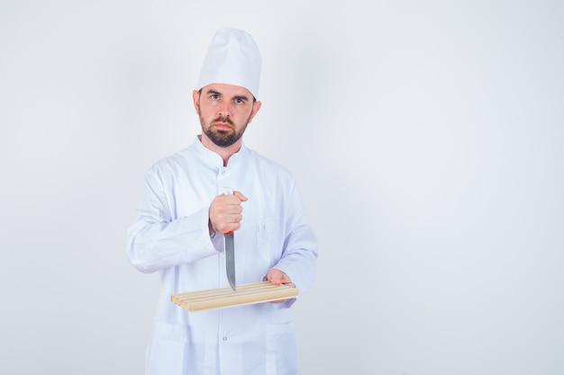 Jovem chef masculino segurando a placa de corte e a faca em uniforme branco e olhando com raiva, vista frontal.
