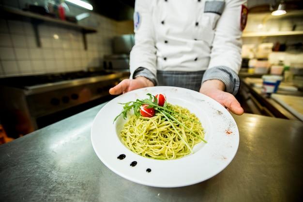 Jovem chef servir e decorar espaguete