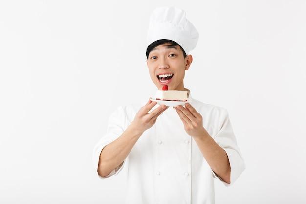 Jovem chefe chinês com uniforme branco de cozinheiro, sorrindo para a câmera enquanto segura o prato com o saboroso cheesecake isolado na parede branca