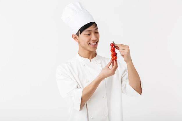 Jovem chefe chinês com uniforme branco de cozinheiro, sorrindo para a câmera, segurando vegetais de tomate isolados sobre a parede branca