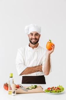 Jovem chefe de uniforme segurando um papel doce enquanto cozinha salada de legumes na tábua de madeira isolada sobre a parede branca
