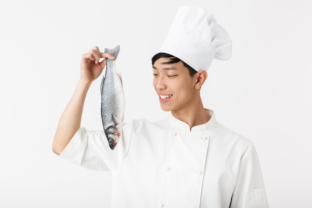 Jovem chefe positivo em uniforme de cozinheiro branco e chapéu sorrindo enquanto segura peixe fresco cru isolado sobre uma parede branca