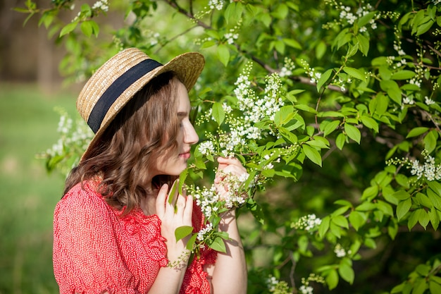 Jovem cheirando uma árvore florescendo