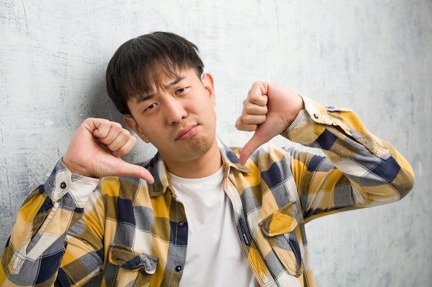 Jovem chinês cara closeup apontando dedos, exemplo a seguir