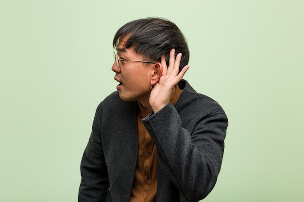 Jovem chinês contra uma parede verde