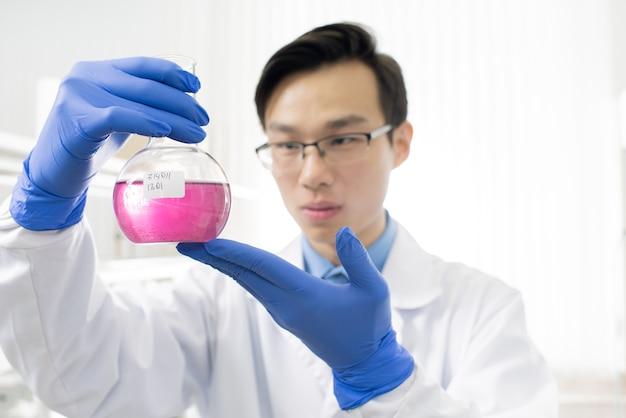 Jovem chinês de jaleco branco e luvas de proteção olhando para uma substância química líquida rosa no bico enquanto a estuda em laboratório