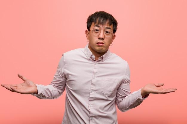 Jovem chinês duvidando e encolher os ombros os ombros