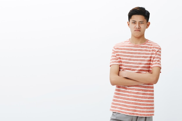 Jovem chinês fofo com uma camiseta listrada parecendo ofendido e zangado, mantendo o insulto por dentro