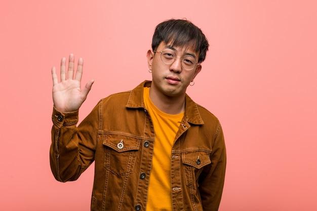 Jovem, chinês, homem, desgastar, um, casaco, mostrando, numere cinco