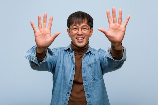 Jovem chinês mostrando o número dez