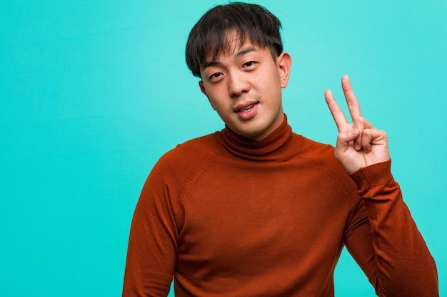 Jovem chinês mostrando o número dois