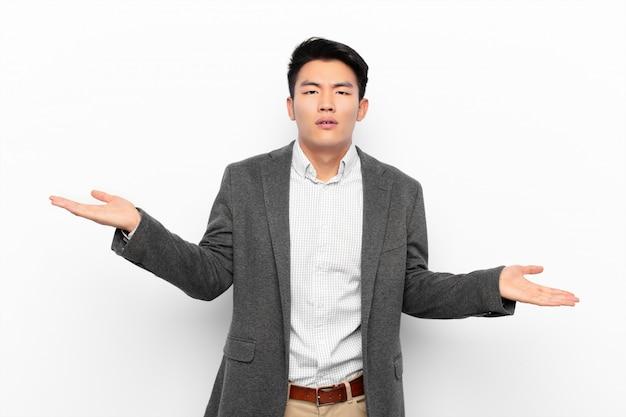 Jovem chinês olhando intrigado, confuso e estressado, pensando entre diferentes opções, sentindo-se incerto contra a parede de cor lisa