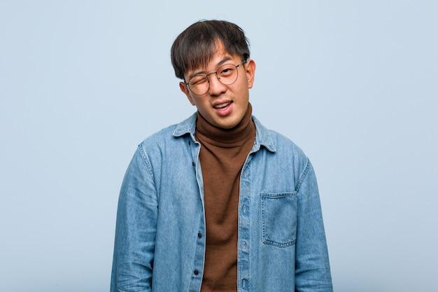 Jovem chinês piscando, gesto engraçado, amigável e despreocupado